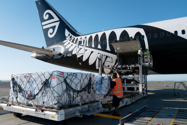 Air New Zealand Cargo staff loading a PMC onto 787 aircraft
