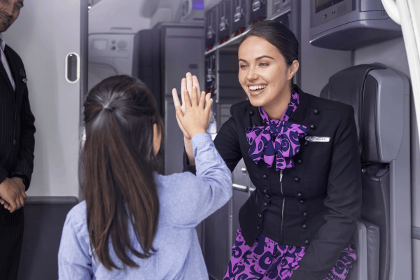 Onboard-flight-attendant-greeting-child-4302-1200x800
