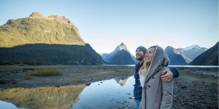 Couple enjoying mountain scenery, Milford Sound