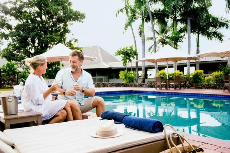 Couple with drinks by the pool, Novotel Fiji, Fiji.