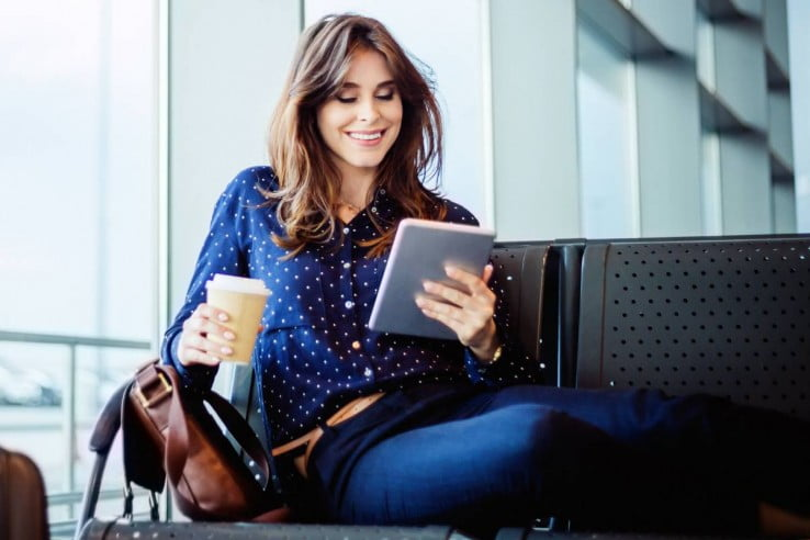 Woman reading tablet at airport.