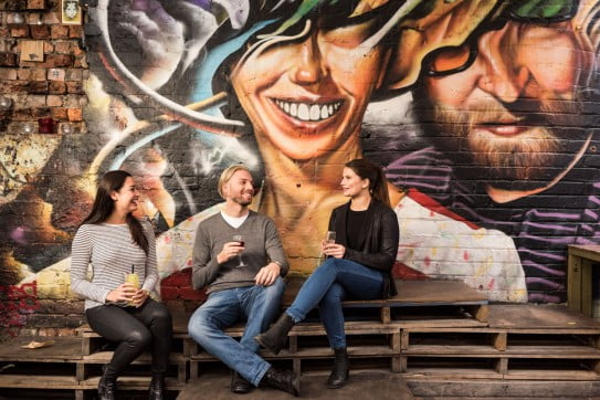 Friends laughing in front of street art, Melbourne, Australia.
