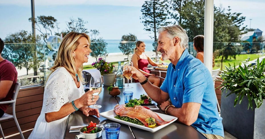 A couple enjoying a seafood lunch at City Beach, Perth.