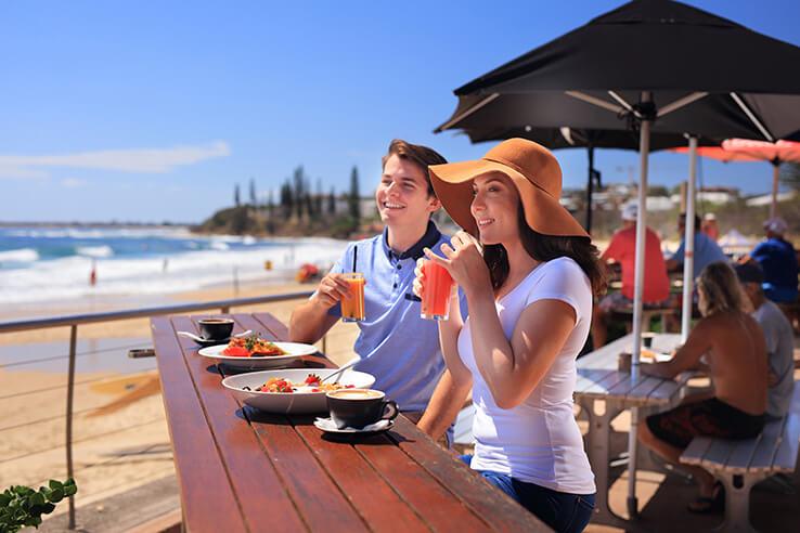 Couple eating at Alex Heads Surf Club, Sunshine Coast, Australia.