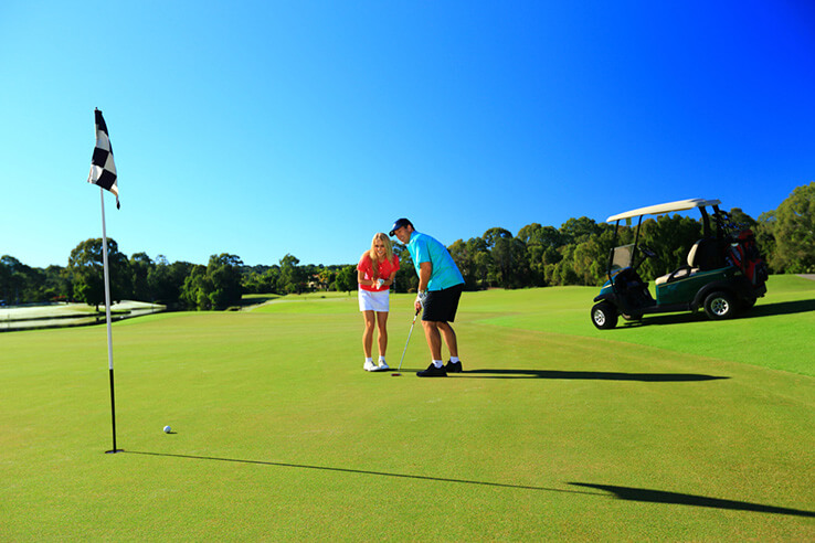 Couple on golf course, Sunshine Coast, Australia.