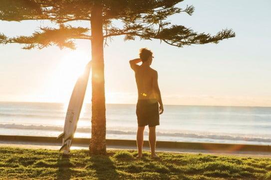 Surfer gazing over Manly Beach, Sydney, Australia.