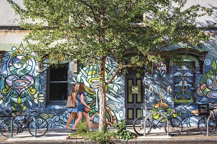 Women walking passed street art, Newtown, Australia.