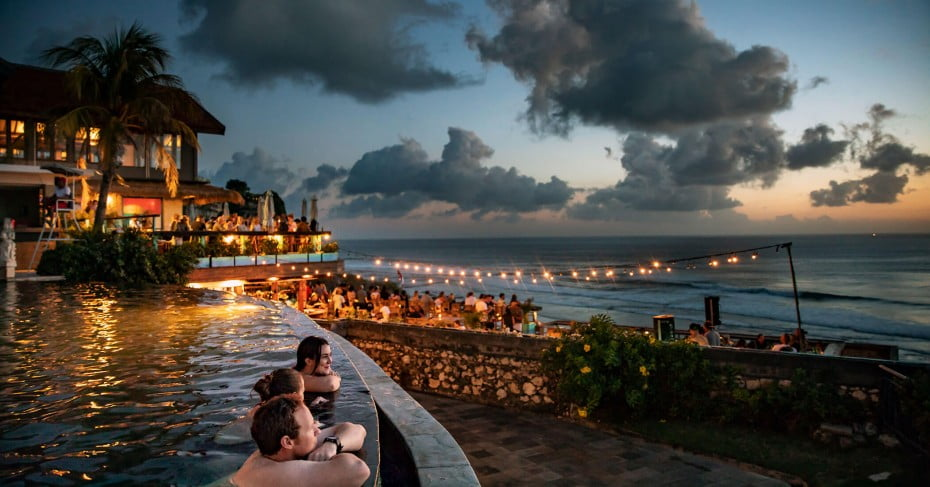 Evening pool with friends by restaurant and beach, Bali, Indonesia.