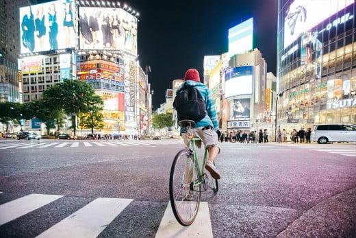 Cyclist at crossroad, Shibuya, Tokyo, Japan.