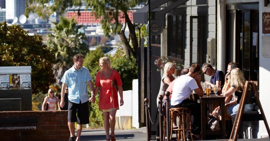 A couple walking past a busy bar in Ponsonby, Auckland.