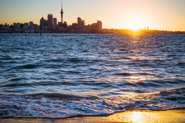 New Zealand Auckland skyline at sunset from Devonport Beach.