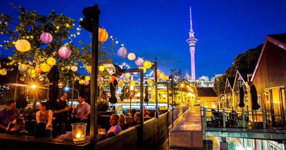 The Auckland Sky Tower and a busy bar at night.
