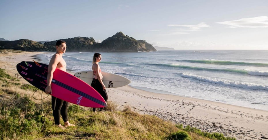 Surfers on the beach at Great Barrier Island.