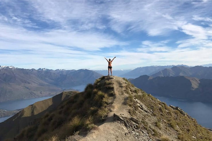 Hiker at the top of Roys Peak, Wanaka.
