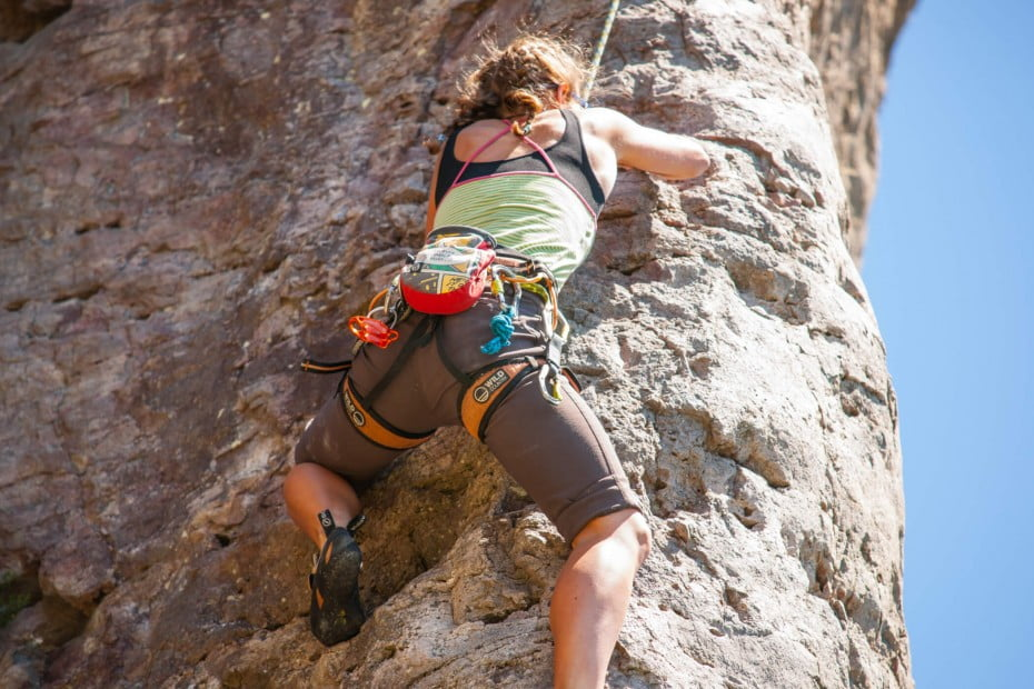 Adventurous person rock climbing up a shear face of Mount Maunganui on New Zealand's, North Island