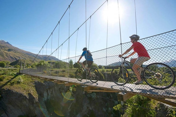 Couple cycling across Edgar Bridge, Queenstown.