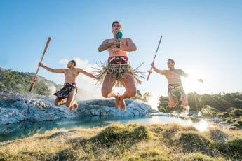 Three Maori men in mid air, Rotorua, New Zealand.