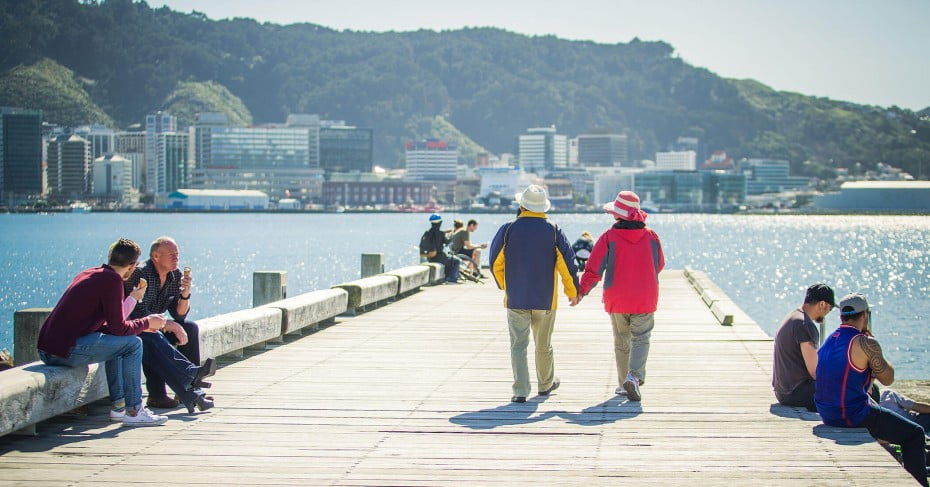 Couple walking hand in hand, Wellington waterfront, New Zealand.