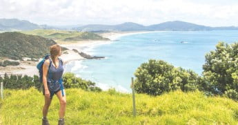Woman walking Bream Head Coastal Track, Northland, New Zealand