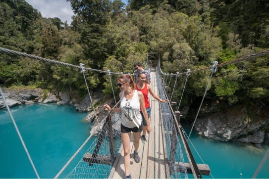 Friends crossing the swing bridge, Hokitika River, West Coast, NZ