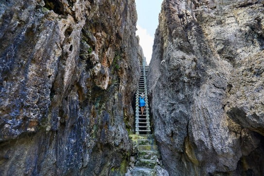 Lady in blue climbing up a ladder between rocks, Niue, Pacific Islands.