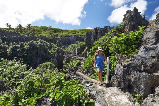 Lady in blue walking through rocky terrain, Niue, Pacific Islands.