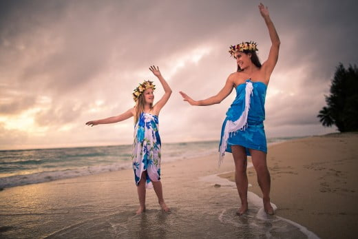 Girl and woman dancing on beach, Rarotonga, Cook Islands.