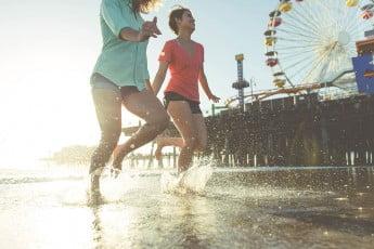 Girls running on beach, Santa Monica, Los Angeles, United States.