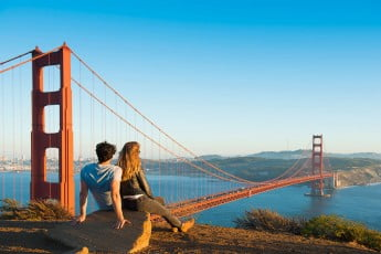 Couple looking at Golden Gate Bridge, San Francisco, USA.