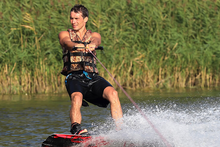 Athlete wakeboarding on a river and looking away, in Houston, USA