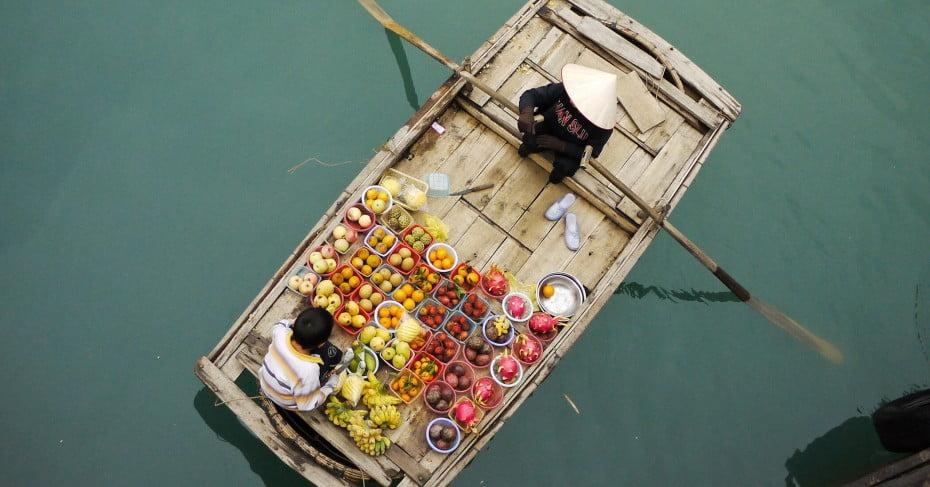 Fruit vendor on boat, Ha Long Bay, Vietnam.