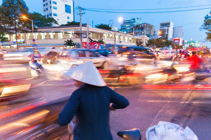 Woman crossing road, Vietnam.