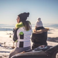 Two women sitting on a car in the snow.