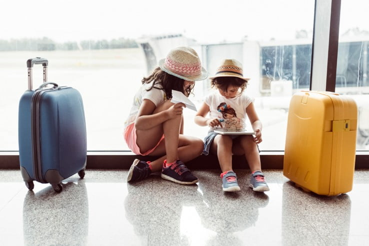 Children at airport with baggage.