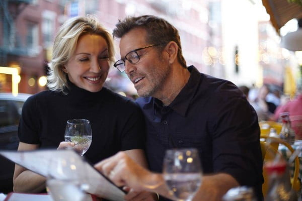 Couple reading menu at urban cafe in New York, United States