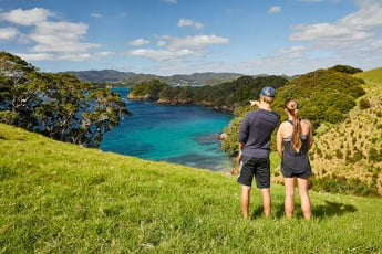 Couple looking at view towards water, Bay of Islands, New Zealand