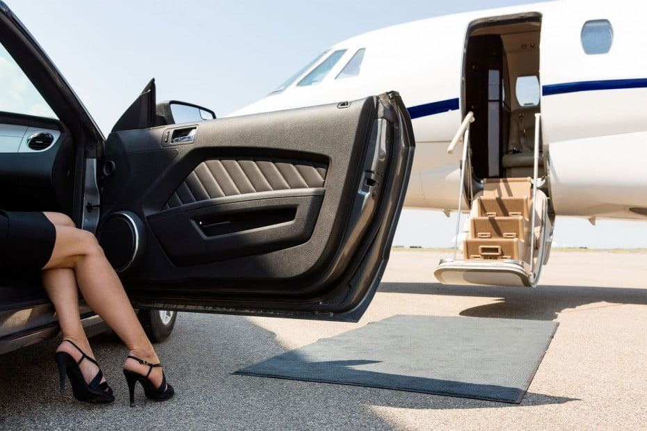 Woman stepping out of car to board private plane